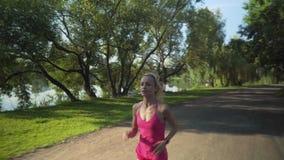 Mujer caucásica joven que activa en parque público cerca del río metrajes