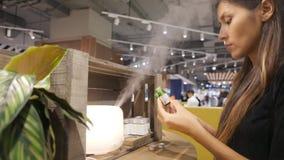 Mujer caucásica joven que elige el aceite del aroma para el difusor en alameda de compras 4K almacen de metraje de vídeo