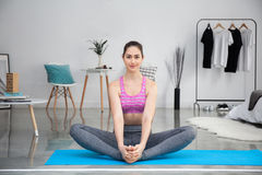 Mujer caucásica joven que estira y que hace yoga en casa Fotos de archivo