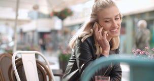 Mujer caucásica joven que habla en el teléfono en una ciudad Imagenes de archivo