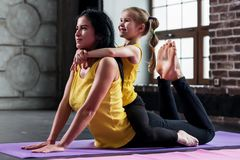 Mujer caucásica joven que hace estirando el ejercicio para la espina dorsal así como un niño que se sienta cómodamente en ella en imágenes de archivo libres de regalías