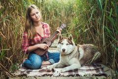 Mujer caucásica joven que juega el ukelele con el perro esquimal imágenes de archivo libres de regalías