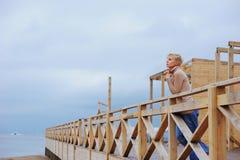 Mujer caucásica joven que se coloca en un pabellón en la orilla de mar que se inclina sobre la verja Imagenes de archivo