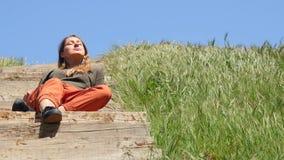 Mujer caucásica joven que se sienta en la escalera de madera y que disfruta de vida en tiempo de la sol metrajes