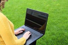 Mujer caucásica joven que usa el ordenador portátil en la naturaleza Foto de archivo libre de regalías