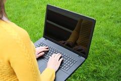Mujer caucásica joven que usa el ordenador portátil en la naturaleza Fotos de archivo libres de regalías