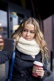 Mujer caucásica joven rubia feliz hermosa que toma un selfie en smartphone al aire libre en parque en otoño Imagen de archivo