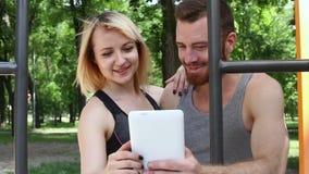 Mujer caucásica joven y un hombre barbudo que hojea Internet en una tableta blanca