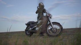 Mujer caucásica linda en una chaqueta de cuero y un casco negros que montan una motocicleta clásica La muchacha quita la situació almacen de video