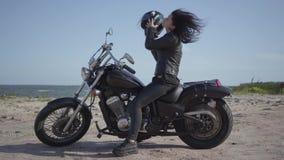 Mujer caucásica linda en una chaqueta de cuero y un casco negros que se sientan en la motocicleta La muchacha quita el casco y se metrajes