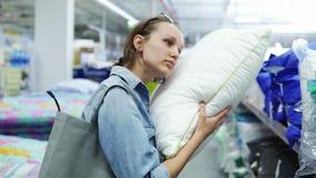 Mujer caucásica linda, positiva en la tienda Concepto de las compras Tome una almohada suave del estante y ponga su cabeza encend almacen de metraje de vídeo