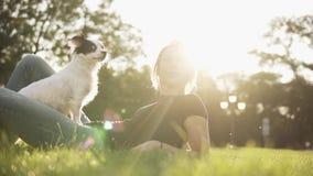 Mujer caucásica linda que miente en la hierba con su pequeño perro blanco y negro que se sienta en sus piernas La caricia del due almacen de video
