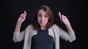 Mujer caucásica morena de mediana edad que gesticula muestras de los cruzar-fingeres de mostrar esperanza en cámara en fondo negr almacen de video
