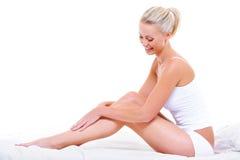 Mujer caucásica que frota ligeramente sus piernas de la belleza Foto de archivo