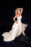 Mujer caucásica que modela el vestido de boda, zapatos, Blonde, fondo negro Foto de archivo libre de regalías