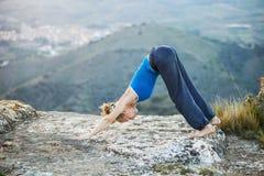 Mujer caucásica que realiza actitud hacia abajo de la yoga del perro Foto de archivo