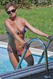 Mujer caucásica que se coloca en las escaleras de nadar la piscina al aire libre Imagen de archivo libre de regalías