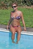 Mujer caucásica que se sienta al borde de nadar la piscina al aire libre Imágenes de archivo libres de regalías