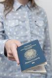 Mujer caucásica que sostiene un pasaporte brasileño Imagenes de archivo