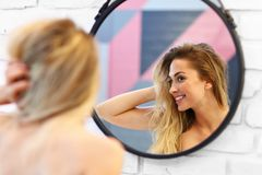 Mujer caucásica rubia hermosa que presenta en cuarto de baño con el pelo mojado imagenes de archivo