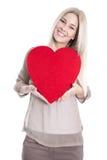 Mujer caucásica rubia joven feliz aislada que lleva a cabo el corazón rojo. Fotografía de archivo