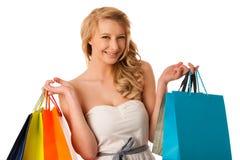 Mujer caucásica rubia joven hermosa que celebra compras vibrantes Foto de archivo libre de regalías