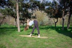 Mujer caucásica sana joven que hace ejercicio de la aptitud de la yoga en el parque Imágenes de archivo libres de regalías