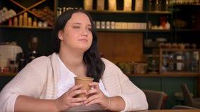 Mujer caucásica soñadora grande que piensa y que sostiene su bebida en café almacen de video