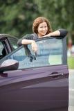 Mujer caucásica sonriente alegre que se coloca detrás de puerta de coche Fotografía de archivo