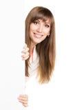 Mujer caucásica sonriente de los jóvenes que lleva a cabo al tablero blanco Foto de archivo