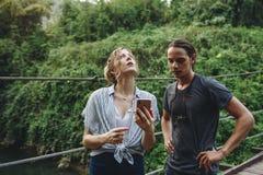 Mujer caucásica y hombre que tienen una mala señal celular en el concepto del problema del viaje de la naturaleza Fotos de archivo
