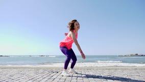 Mujer cauc?sica del ajuste atractivo joven que se divierte que salta con las manos en el aire en el muelle de la playa metrajes