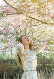 Mujer cauc?sica hermosa preciosa en el vestido que se coloca de presentaci?n en el fondo de la cereza floreciente de Jap?n fotos de archivo