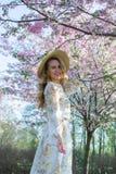 Mujer cauc?sica hermosa preciosa en el vestido que se coloca de presentaci?n en el fondo de la cereza floreciente de Jap?n imagen de archivo