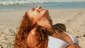 Mujer cauc?sica joven hermosa en el bikini que se relaja en la playa en la sol almacen de metraje de vídeo