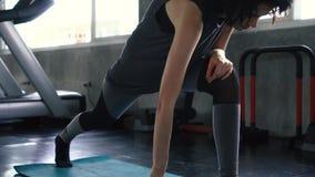 Mujer cauc?sica joven que estira sus piernas en el piso del gimnasio Muchacha apta femenina que hace calentamiento y la elaboraci metrajes