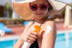 Mujer cauc?sica que pone la crema solar en su hombro por la piscina bajo sol el d?a de verano Factor de protecci?n de Sun en vaca foto de archivo