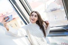 Mujer caucásica hermosa cerca de la ventana, haciendo caras, sonriendo y haciendo selfie la mañana Fotos de archivo libres de regalías