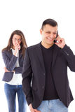 Mujer celosa que mira a su socio que charla en el teléfono Foto de archivo libre de regalías