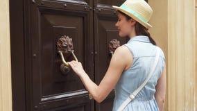 Mujer cerca de la manija de madera vieja del control de la puerta en la forma de león Golpe femenino del viajero en puerta en la  almacen de video