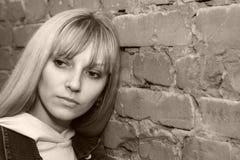 Mujer cerca de la pared de ladrillo Imagen de archivo libre de regalías