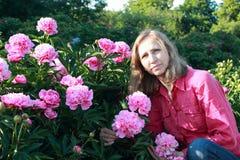Mujer cerca de peonías de un arbusto Foto de archivo