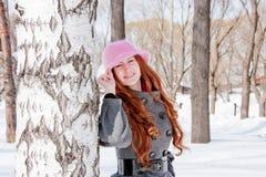 Mujer cerca de un abedul en invierno en un parque Foto de archivo libre de regalías