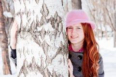 Mujer cerca de un abedul en invierno en un parque Imagen de archivo libre de regalías