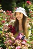 Mujer cerca de un arbusto con las rosas foto de archivo
