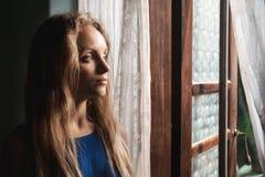 Mujer cerca de una ventana Fotos de archivo libres de regalías