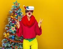 Mujer cerca del árbol de navidad con los vidrios de VR que muestran la victoria Fotos de archivo libres de regalías