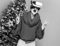 Mujer cerca del árbol de navidad con los vidrios de VR que muestran la victoria Imágenes de archivo libres de regalías