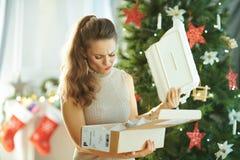 Mujer cerca del árbol de navidad que saca el plato quebrado del paquete fotografía de archivo libre de regalías