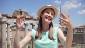 Mujer cerca del foro romano usando móvil en la cámara lenta Turístico femenino teniendo charla video vía el app en línea almacen de video